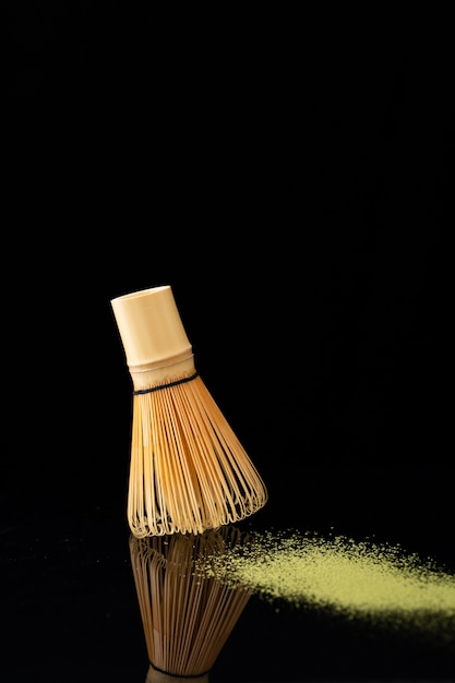 Una piccola scopa che spazza la polvere gialla sul nero Foto Gratuite