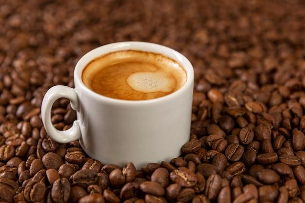 Una piccola tazza di caffè bianca si trova sui chicchi di caffè. piacere fragrante. Foto Premium