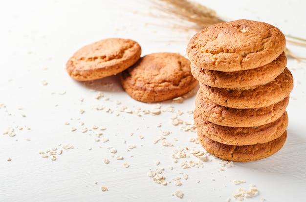 Una pila di biscotti di farina d'avena con fiocchi d'avena su un tavolo di legno bianco Foto Premium