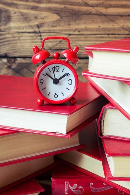 Una pila di libri con copertina rigida e una sveglia su un tavolo di legno. copia spazio per il testo Foto Premium