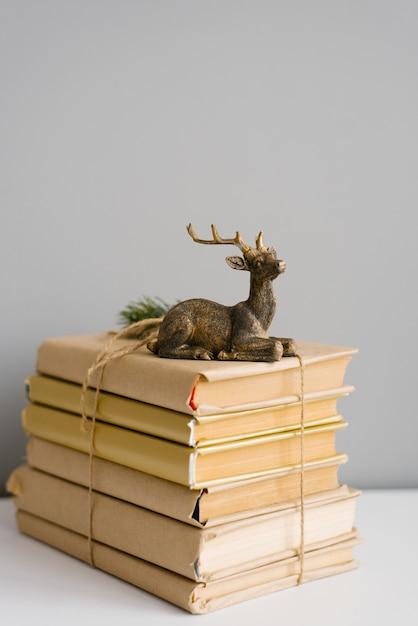 Una pila di libri in una copertina di artigianato, legata con spago, sui libri è una statuetta di un cervo seduto Foto Premium