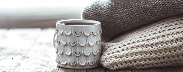 Una pila di maglioni e una tazza di tè Foto Gratuite