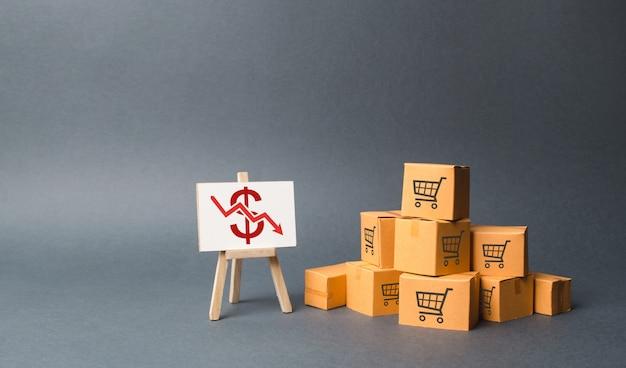 Una pila di scatole di cartone e supporto con una freccia rossa verso il basso. declino nella produzione di beni Foto Premium