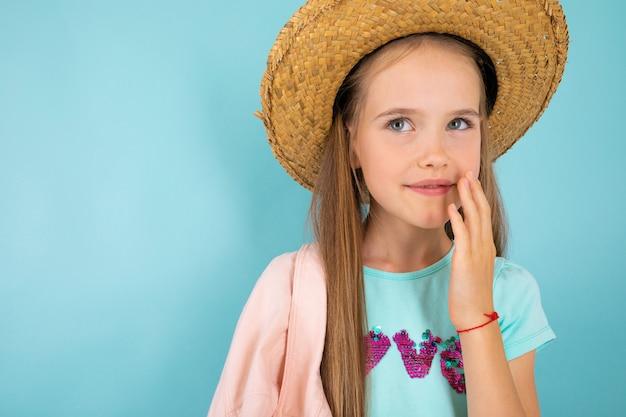 Una ragazza adolescente con gli occhi grigi, bel sorriso e con un cappello isolato su blu Foto Premium