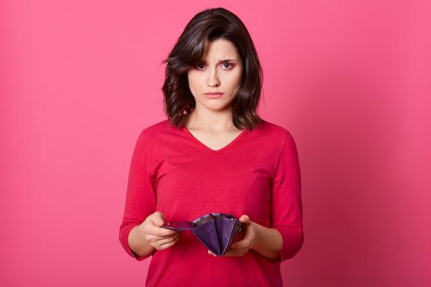 Una ragazza adulta molto triste con la borsa vuota che guarda direttamente alla macchina fotografica, non ha soldi dopo lo shopping, ha problemi finanziari, non ha contanti di cattivo umore. Foto Gratuite