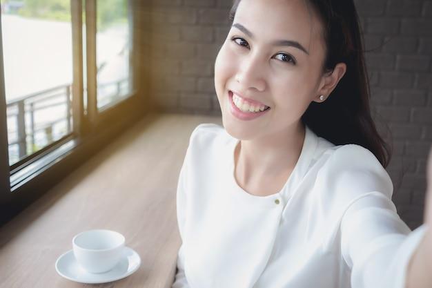 Una ragazza asiatica si sta facendo una foto durante una pausa durante il giorno Foto Premium