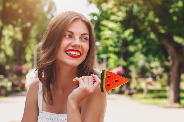 Una ragazza cammina nel parco con un lecca-lecca sotto forma di anguria. ragazza in cappello di paglia sorridente nel parco Foto Premium