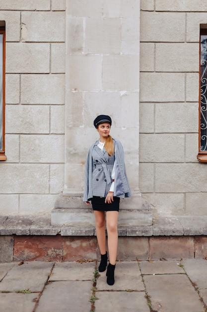 Una ragazza carina e carina in un completo elegante gira per la città e si mette in posa Foto Premium