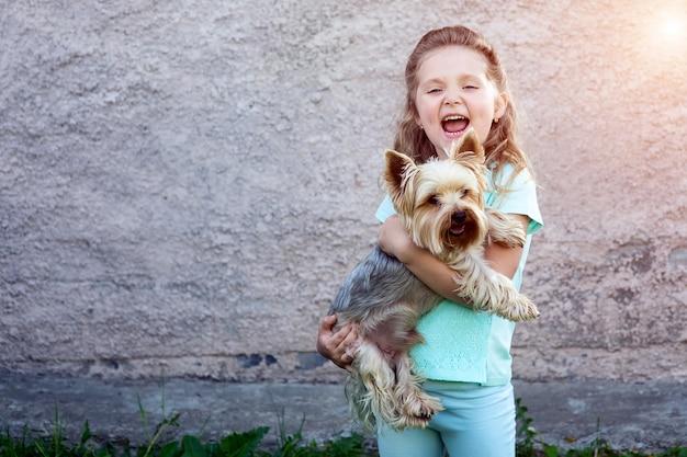 Una ragazza carina in una t-shirt blu con fossette sulle guance in possesso di un cane e sorridente Foto Premium
