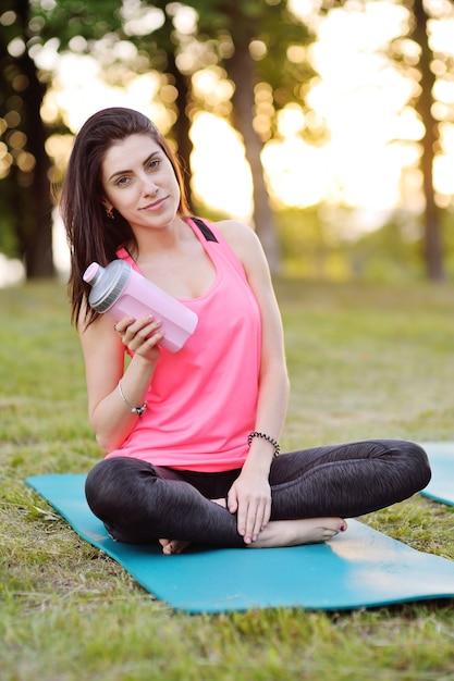 Una ragazza che fa sport con una bottiglia d'acqua rosa o con un cocktail di proteine Foto Premium
