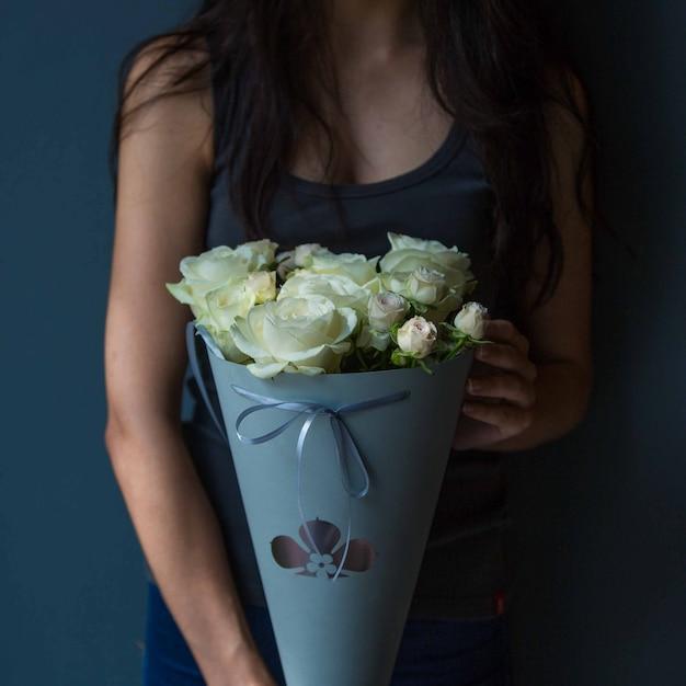 Una ragazza che mantiene elegante bouquet portatile di rose bianche in una stanza singola Foto Gratuite