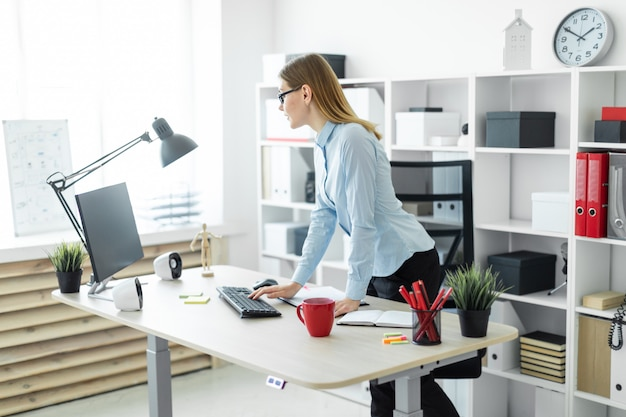 Una ragazza con gli occhiali si trova vicino al tavolo e stampa sulla tastiera. Foto Premium