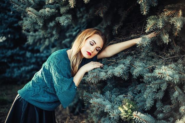Una ragazza con i capelli biondi e gli occhi azzurri in un maglione verde in un parco vicino all'albero di abete verde blu Foto Premium