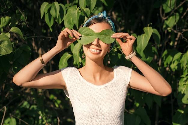 Una ragazza con le parentesi graffe sorride allegramente in una soleggiata giornata estiva, chiude gli occhi con le foglie verdi. Foto Premium