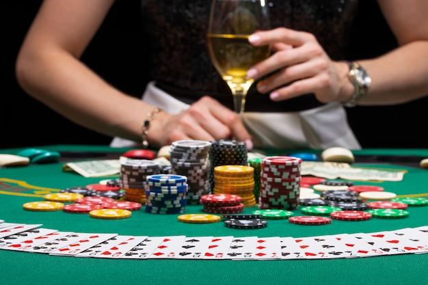 Una ragazza con un bicchiere di vino che gioca a poker Foto Premium