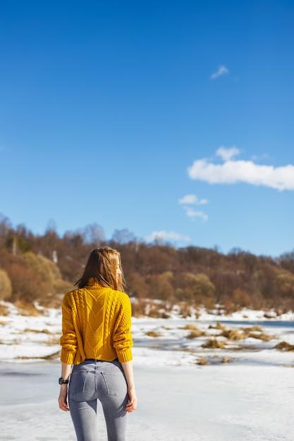 Una ragazza con un maglione giallo con un taglio di capelli corto sta sul ghiaccio del fiume. Foto Premium