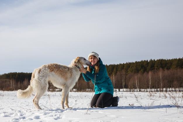 Una ragazza con una giacca da sci verde in ginocchio e un segugio bianco russo Foto Premium