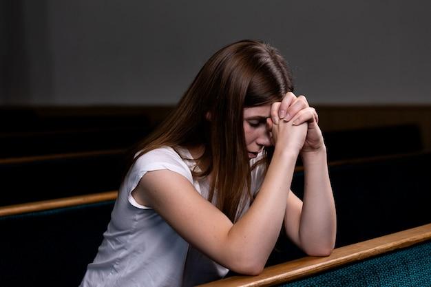 Una ragazza cristiana triste in camicia bianca è seduta e prega con umile cuore in chiesa Foto Premium