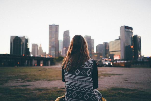 Una ragazza del viaggiatore sta guardando l'orizzonte della città e il tramonto Foto Premium
