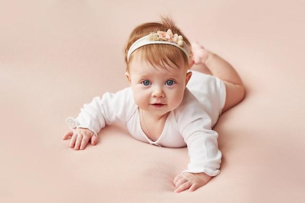 Una ragazza di quattro mesi si trova su uno sfondo rosa chiaro Foto Premium