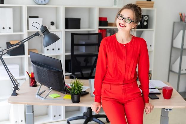 Una ragazza è in piedi appoggiata su un tavolo in ufficio. Foto Premium