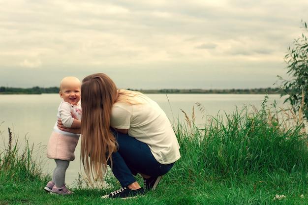 Una ragazza impara a camminare con sua madre in natura. mamma e figlia, apprendimento e sviluppo. i primi passi del bambino. momenti felici di vita. Foto Premium
