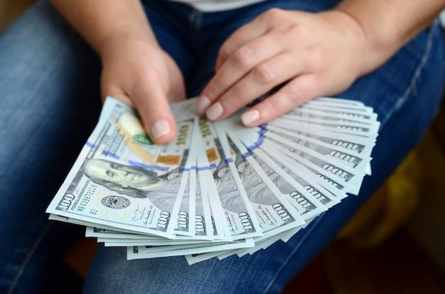 Una ragazza in possesso di un fan di banconote da un dollaro Foto Premium