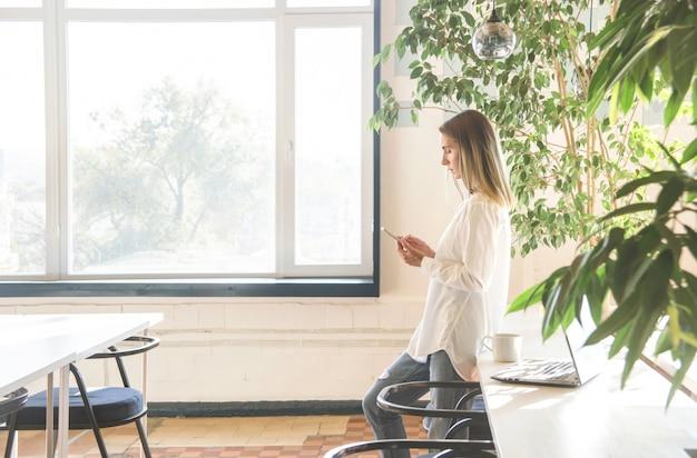 Una ragazza in una camicia bianca sta guardando smartphone tra lavoro di libero professionista. Foto Premium