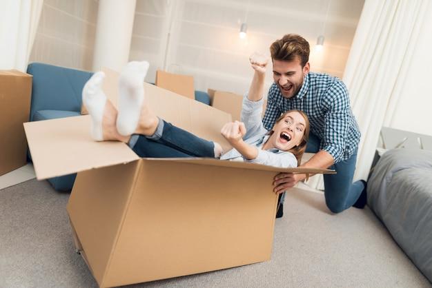 Una ragazza in una scatola e un ragazzo la sta facendo rotolare per l'appartamento Foto Premium