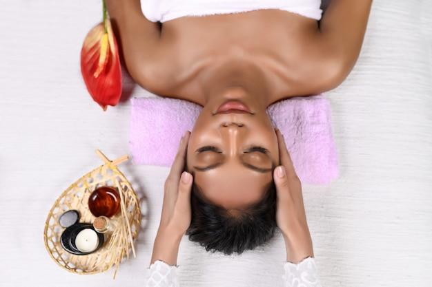 Una ragazza interrazziale sorridente giace con gli occhi chiusi su un rullo rosa sotto la testa in un asciugamano su un lettino da massaggio e riceve un massaggio alla testa Foto Premium