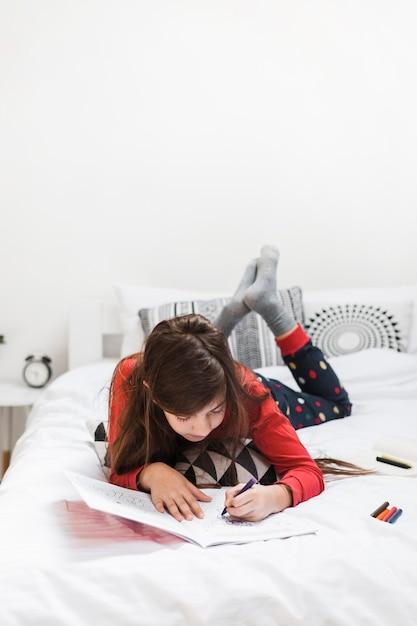 Una ragazza sdraiata sul letto di disegno con pastelli colorati scaricare foto gratis - Foto di donne sul letto ...