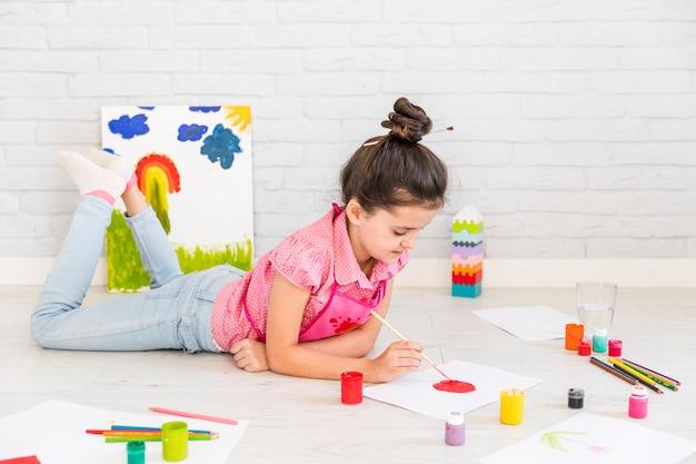 Una ragazza sdraiata sul pavimento dipinto su carta bianca con pennello Foto Gratuite
