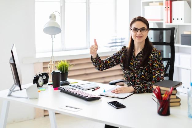 Una ragazza seduta in ufficio al computer scrivania e mostra bene il segno. Foto Premium