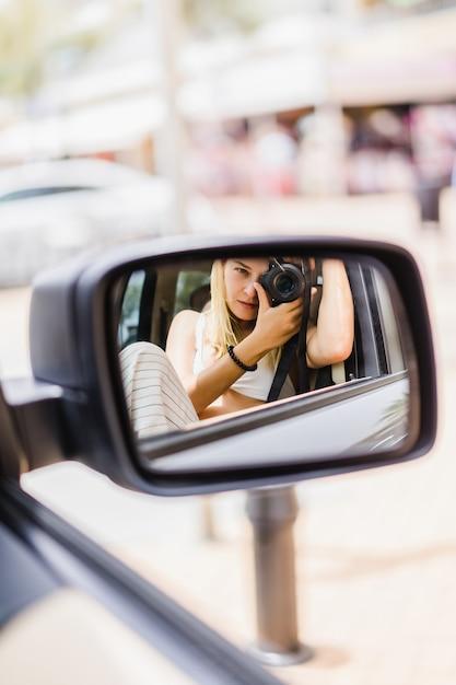 Una ragazza si fa una foto di se stessa in uno specchio per auto Foto Gratuite
