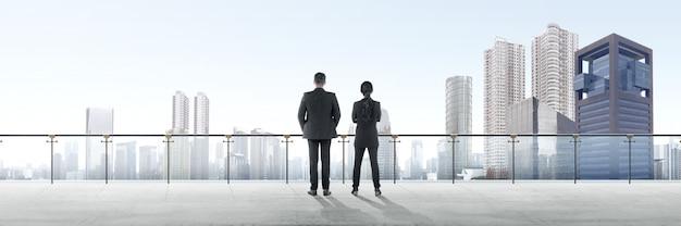 Una retrovisione di due genti di affari asiatiche che stanno sul terrazzo moderno e che esaminano vista Foto Premium