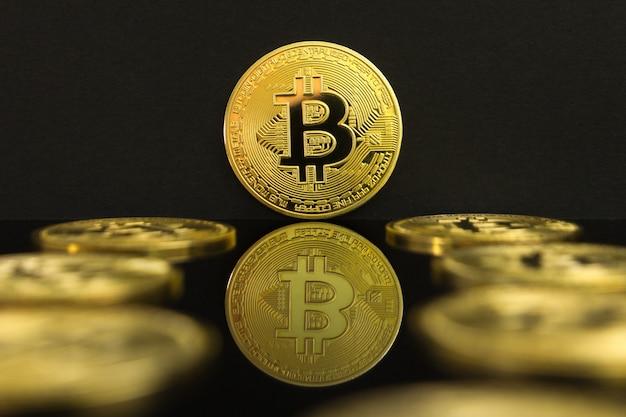 Una riflessione speculare delle monete d'oro di un btc. la moneta del bitcoin è su un tavolo nero e sfondo nero. Foto Premium