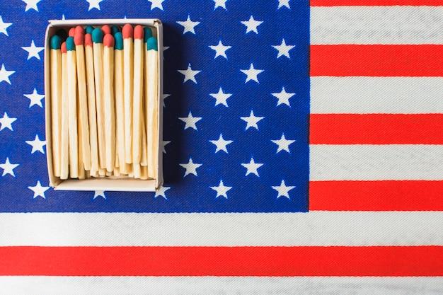 Una scatola aperta del fiammifero sulla bandiera americana dello stato unito Foto Gratuite