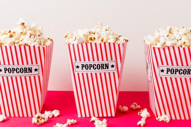 Una scatola di tre popcorn riempita di popcorn su fondo rosa Foto Gratuite