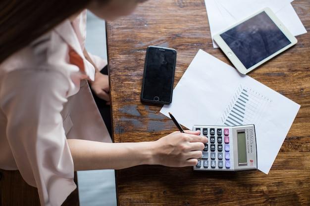 Una scrivania per fare affari con le mani di una giovane donna sta calcolando le entrate e le spese. Foto Premium