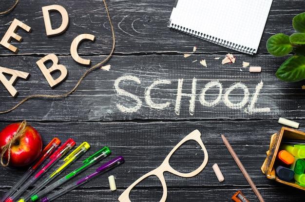 Una scrivania per studenti su una tavola di scuola, uno sfondo di legno scuro fatto di tavole. Foto Premium