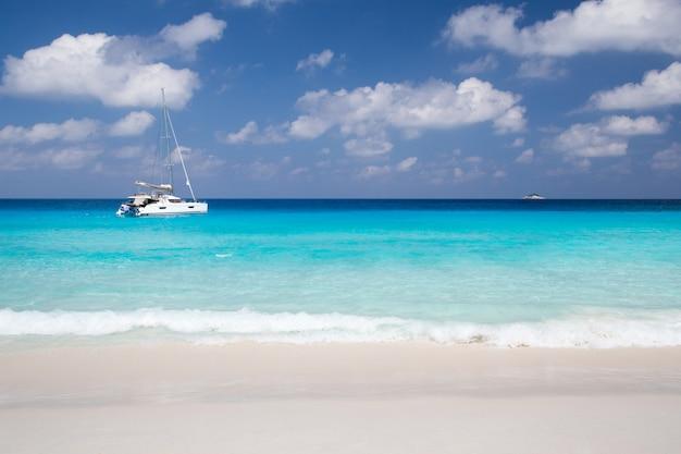 Una spiaggia di sabbia bianca con acqua turchese e pietre Foto Premium