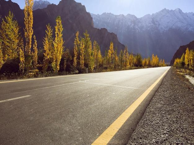 Una strada pavimentata vuota sulla strada principale di karakoram contro la stagione autunnale del mountain range ricoperto neve. Foto Premium