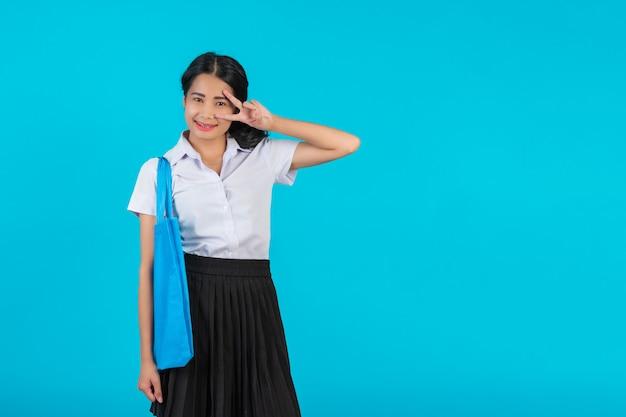 Una studentessa asiatica che gira una borsa di stoffa e mostra vari gesti su un blu. Foto Gratuite
