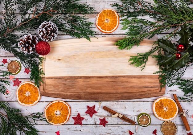 Una tavola di legno con copia spazio per il testo in decorazioni natalizie con albero di natale, arancia secca e cono sullo sfondo Foto Premium