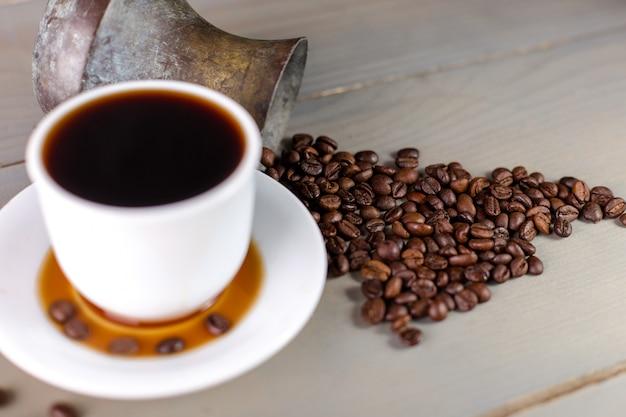 Una tazza bianca di caffè caldo in una dispersione di chicchi di caffè. Foto Premium