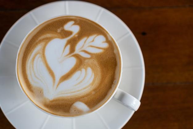 Una tazza di caffè caldo latte art sul tavolo di legno Foto Premium