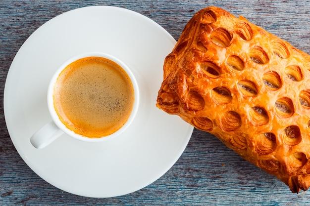 Una tazza di caffè e una torta su un tavolo di legno. Foto Premium
