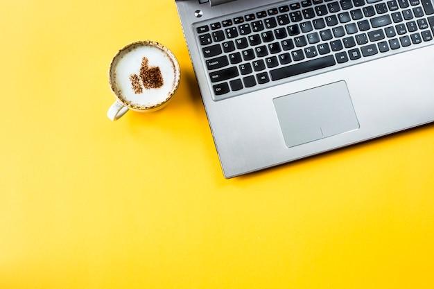 Una tazza di cappuccino su cui è disegnato un sorriso come un pollice in su Foto Premium
