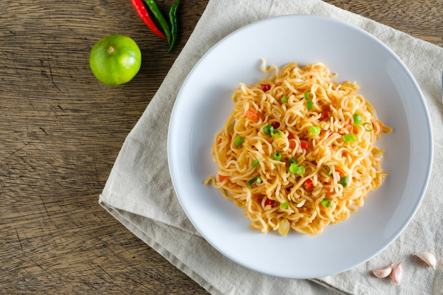 Una tazza di noodles istantanei posizionati su una napery con peperoncino come ingredienti, noodle vista dall'alto e copia spazio Foto Premium