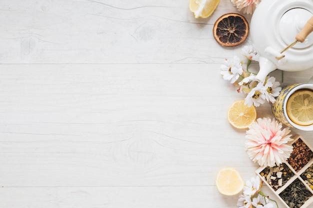 Una tazza di tè al limone; fiori freschi; erbe aromatiche; foglie di tè secche; teiera e fetta di limone sul tavolo di legno bianco Foto Gratuite